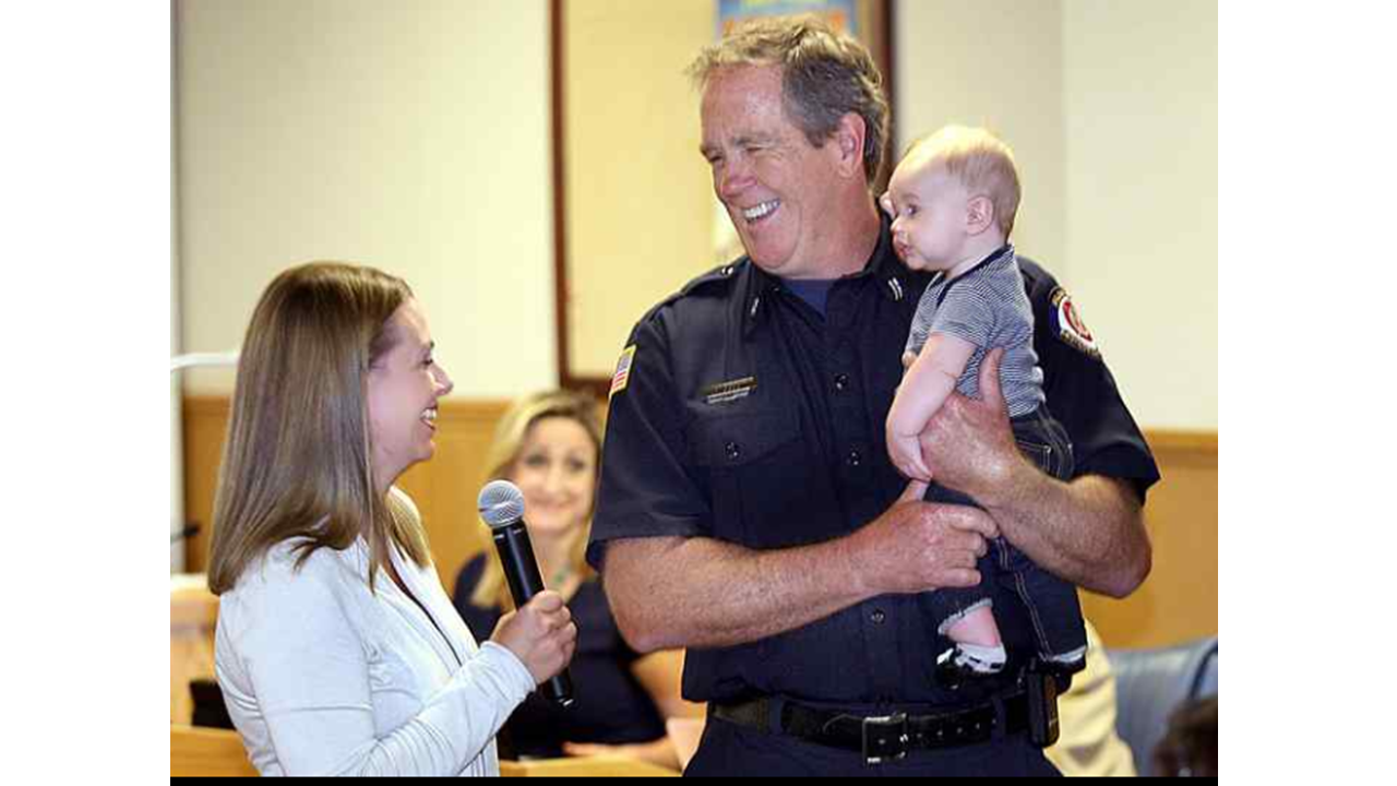 From the Santa Cruz Sentinel, Fire Captain David Ladd holds Lucas Missman at an award ceremony while Michelle thanks him.