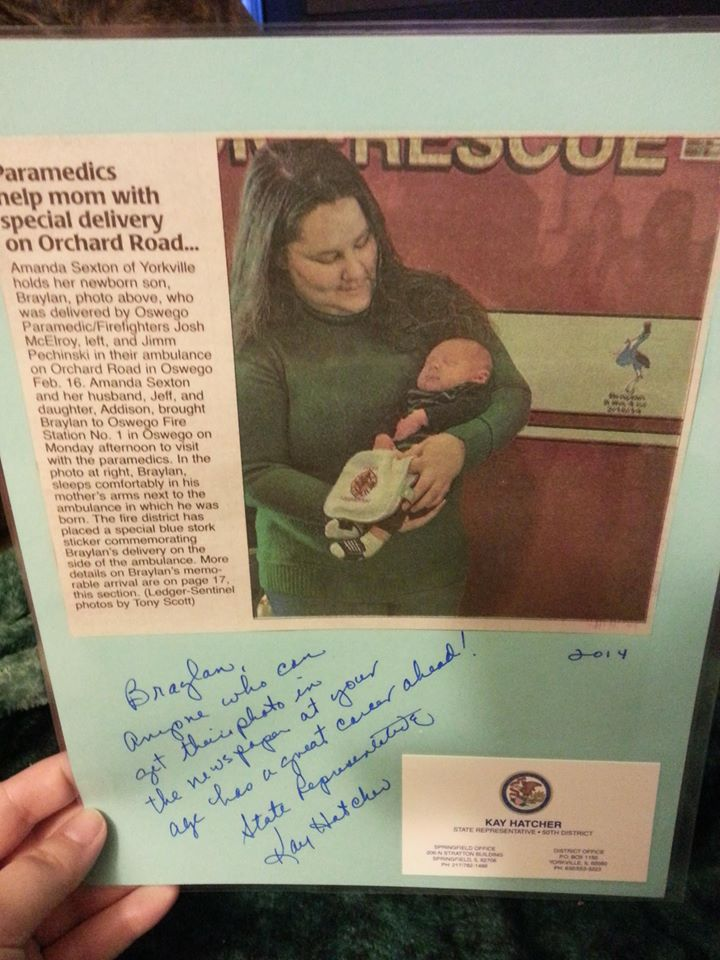 Newspaper clipping of Mom, Amanda, holding her newborn son next to the ambulance where he was delivered. A blue stork decal is on the side of the ambulance commemorates Braylan's birth